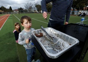 A boy looks forlornly at a grilling tray with just one sausage remaining