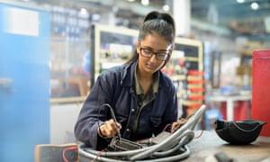 Female apprentice electrician in car factory