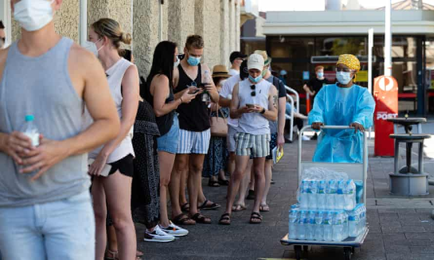 Medical staff hand out water to the long lines of people waiting to be tested for Covid-19 at Royal Perth Hospital on Sunday afternoon.