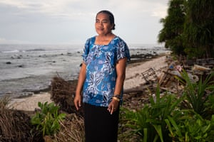 Enna Sione, 41, stands near the ocean which frequently floods her nearby home.