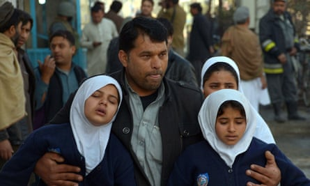 A man helps to evacuate schoolgirls from a school near the Pakistani consulate in Jalalabad.