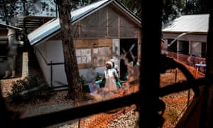 Health workers are seen through a bullet hole left in the window of an Ebola treatment centre in Butembo, which was attacked in March