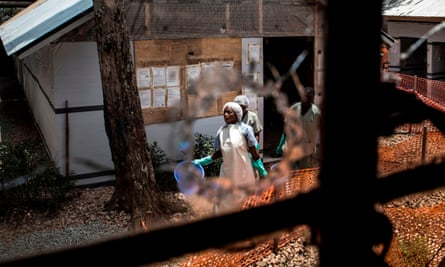 Health workers are seen through a bullet hole left in the window of an Ebola treatment centre in Butembo