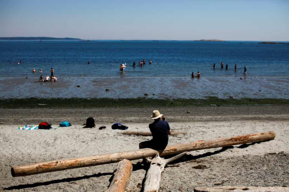 People cool off at Willow's Beach in Victoria, British Columbia. The heatwave has extended across the US north-west and south-western Canada.