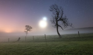 Two glowing sphere hang above a misty field.