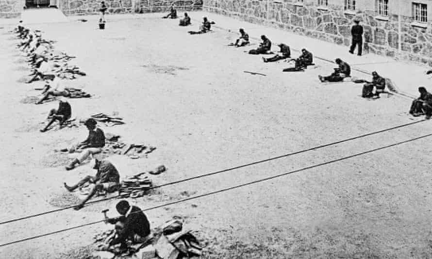 The courtyard at Robben Island Prison, South Africa in the mid-1960's. The line of prisoners on the right are mending old clothes.