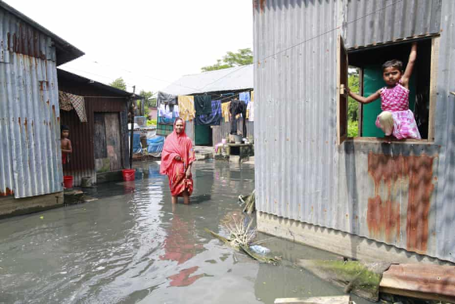 A woman stands in the polluted water that has invaded her home, at Demra in Dhaka