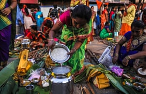 Mumbai, India. A Tamilian woman cooks pongal, a traditional rice dish, during the Thai Pongal festival celebration. The festival gives thanks to the sun and weather for helping obtain a bountiful harvest