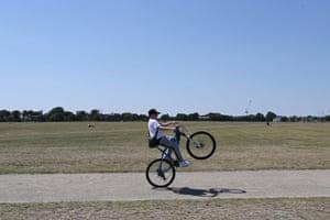 A boy cycles by Blackheath
