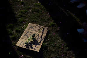 A sign is laid on the grass during a Stop Asian Hate rally at Discovery Green in Houston, Texas, on 20 March, after two mass killings in the US.