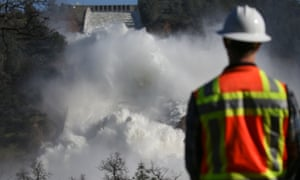 A worker keeps an eye on water coming down the damaged main spillway of the Oroville Dam on February 14, 2017 in Oroville, California. More than 188,000 people were ordered to evacuate after a hole in the emergency spillway in the Oroville Dam threatened to flood the surrounding area.