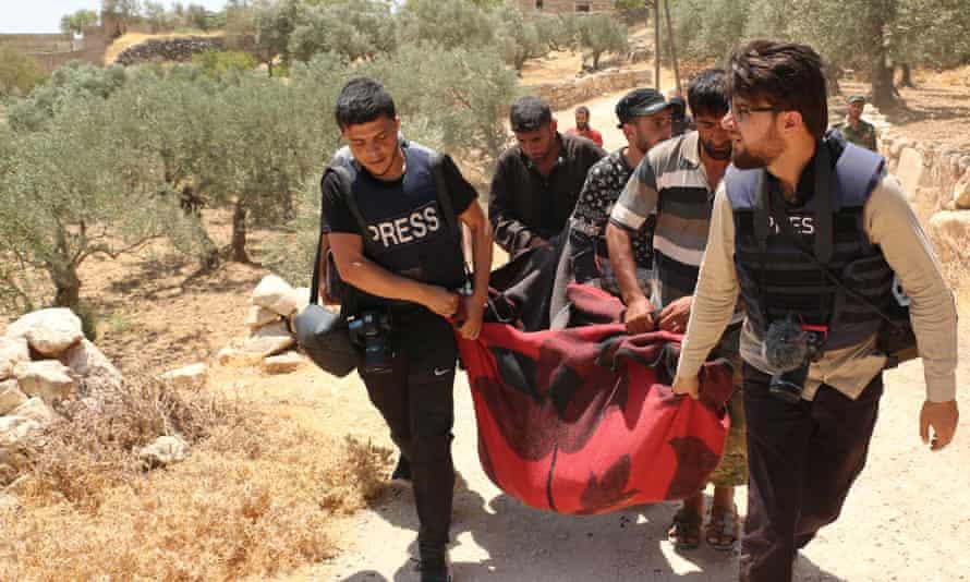 صحفيون يحملون جثة ضحية انتشلت من تحت أنقاض منزل بعد قصف لقوات نظام بشار الأسد وحلفائه في محافظة إدلب في 17 تموز / يوليو.
