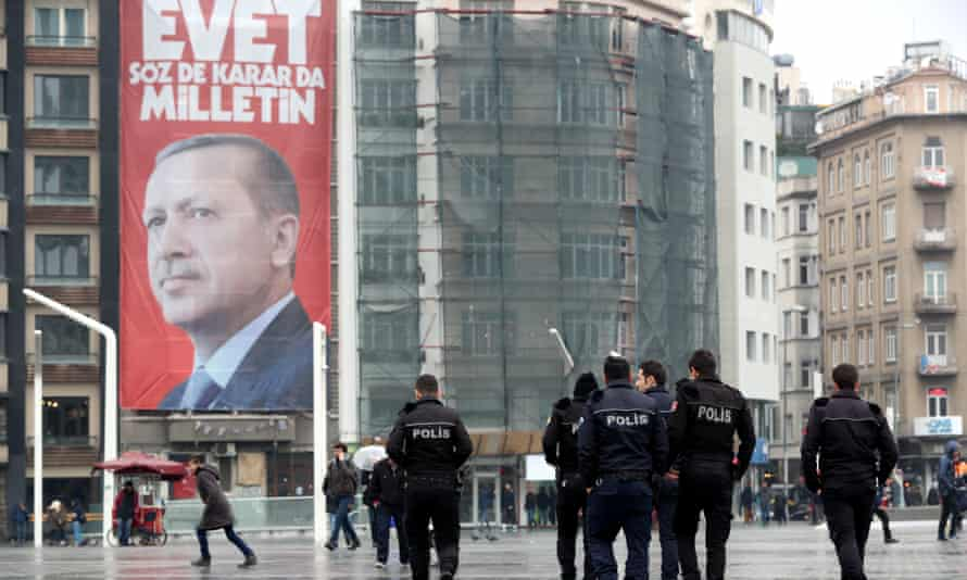 People walk in front of a giant poster of Turkish Recep Tayyip Erdoğan.