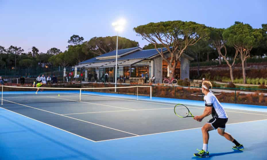 A tennis court and a player at each end