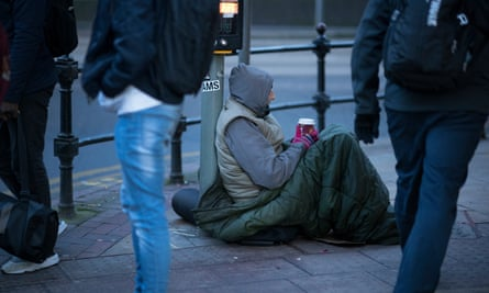 A homeless man begs for small change on the streets of Manchester in December 2017.