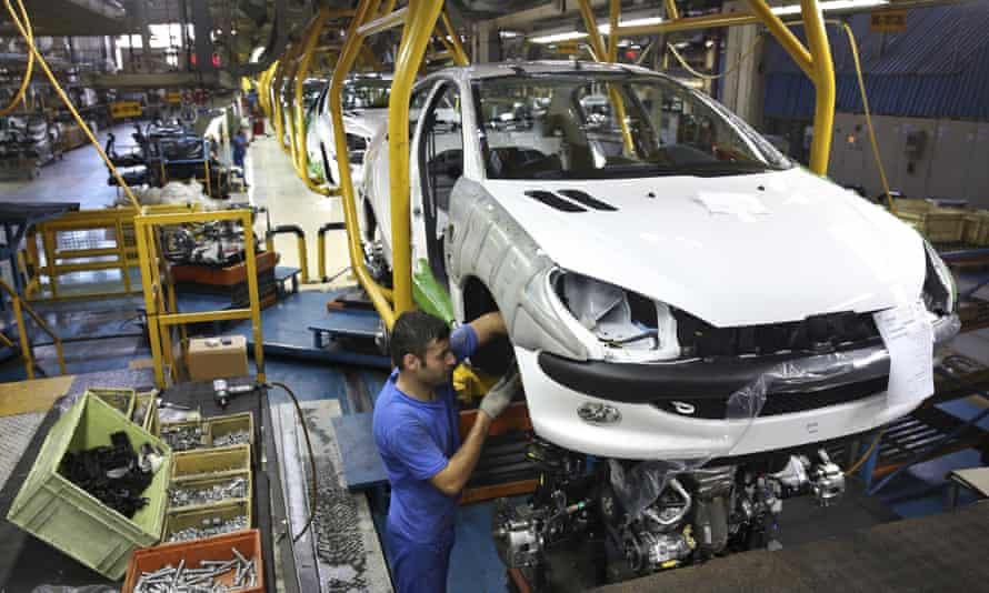 An Iranian worker assembles a Peugeot 206 at the state-run Iran Khodro plant near Tehran