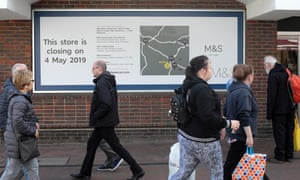People in Ashford walk past sign announcing closure of an M&S branch