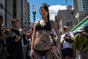 A heavily tattooed Japanese woman poses for photographs near Asakusa Temple