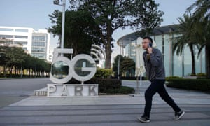 A man talks on his phone as he walks past a sign that says 5G Park