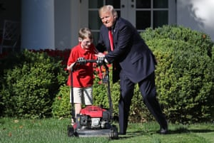 """11-year-old Frank """"FX"""" Giaccio (L) gets a pat on the back from U.S. President Donald Trump (C) while mowing the grass in the Rose Garden of the White House September 15, 2017 in Washington, DC."""