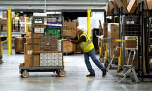 A worker moves merchandise at an Amazon fulfillment center 3 May 2018 in Aurora, Colorado.