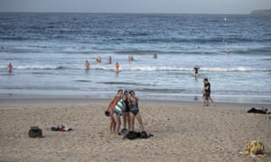 Swimmers take a selfie at Bondi Beach in Sydney on 15 May. Australia's coronavirus lockdown rules and restrictions are gradually being lifted, but when will they end? Get the latest Covid-19 guidelines explained, and your questions answered, like 'How many people can I have in my house?' and 'Can I travel from NSW to Victoria?'