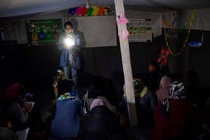 A woman gives evening English lessons to migrants and refugees in a tent without electricity