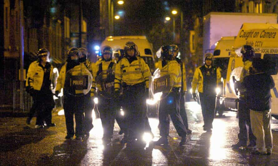 Police in riot gear take to the streets at night in Birmingham in October 2005