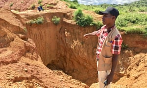 A field worker from local watchdog Foder points out the depth of an abandoned gold mine in eastern Cameroon