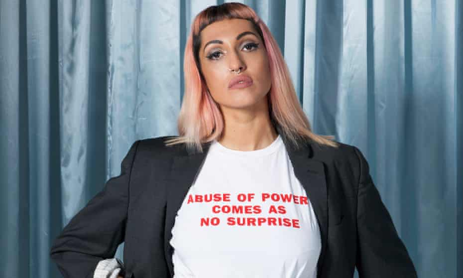 Camilla Mason with long straight pink hair and a white T-shirt saying 'abuse of power comes as no surprise'