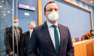 German Health Minister Jens Spahn wearing a face mask leaves following a news conference.