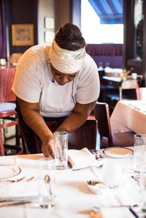 Nikole Randall, server and hostess, sets a table.