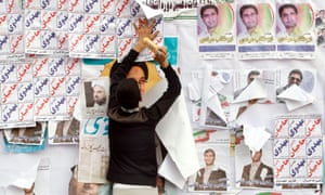 An election campaign worker puts up posters for a parliamentary candidate in the city of Karaj
