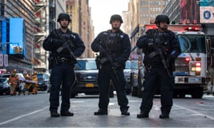 New York City police department officers stand guard near the New York Port Authority bus terminal.
