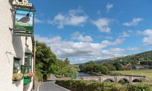 The Grouse Inn and an old stone arched bridge over The River Dee