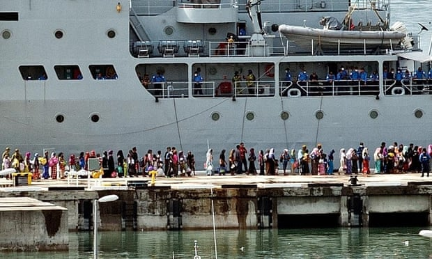 Rohingya women migrants and children stand in a queue to board a Malaysian Navy ship at the naval base in Langkawi on May 14, 2015 to be transferred to a mainland immigration depot