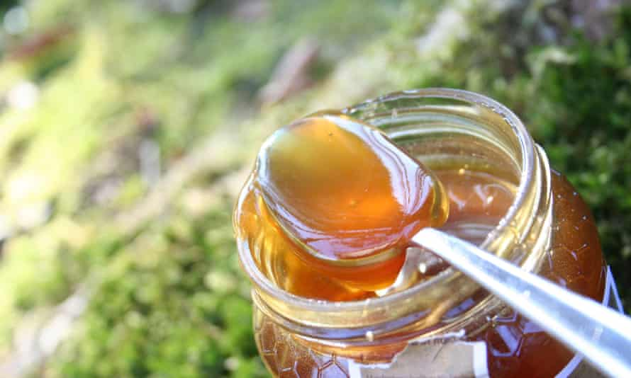 Close-up of spoon in jar of honey