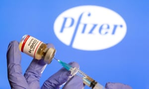 A medical syringe in front of displayed Pfizer logo.