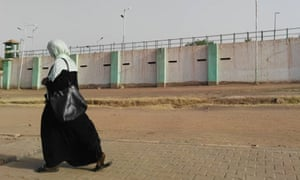 A Sudanese woman walks by the walls of Kobar prison where ousted president Omar al-Bashir is detained in Khartoum