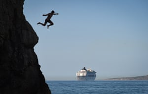 West Lulworth, Dorset A man leaps from Durdle Door against the backdrop of a cruise ship