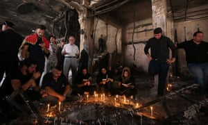 Mourners light candles at the scene of the Baghdad shopping centre that was attacked by suicide bombers on 3 July.