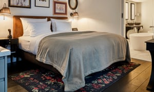 A double bed with four white pillows and a pale grey soft-touch cover