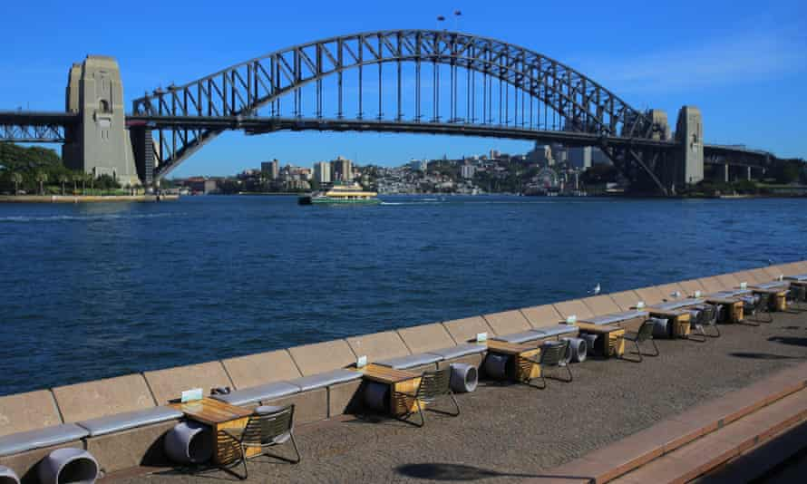 Empty restaurant tables are seen in front of the Sydney Harbour Bridge
