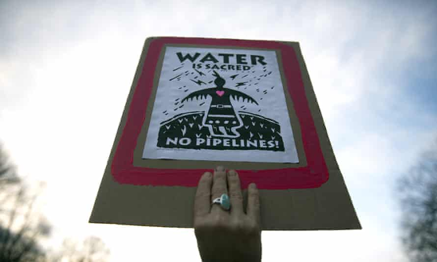 A protester holds a sign during a demonstration against the Dakota Access Pipeline on February 8, 2016.