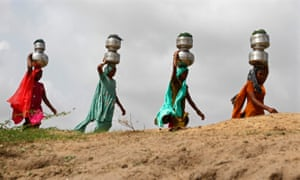Women walk carrying metal pitchers filled with drinking water