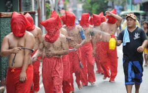 Penitents are sprayed with water to cool them down as they flagellate themselves as part of Lenten observance in Manila, Phillipines