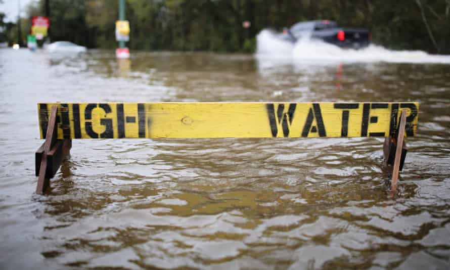 Cars drive through flooded streets behind a High Water sign in Hammond, Louisiana, USA, 11 March 2016. As climate change leads to more extreme weather, more meteorologists will likely take notice.