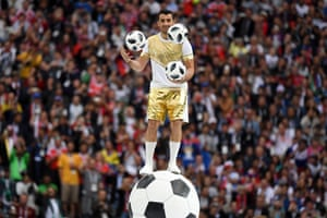 A performer juggles with three footballs during the opening Ceremony