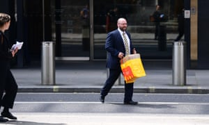 A man leaves the Deutsche Bank building in central London with some belongings on July 8, 2019 in London, England