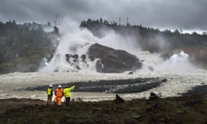 A member of Cal Fire, right, talks to workers on the Oroville Dam project in front of the main spillway in Oroville, California, fears for which forced the evaucation of 200,000 people in February.